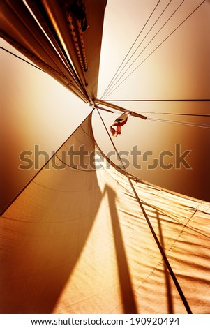 Sails in sunset light, dark orange sky background, summer adventure, traveling on luxury water transport, freedom and extreme sport concept - stock photo