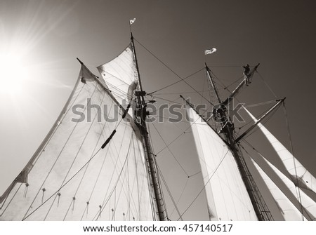 Sails of tall ship with person aloft