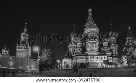 Saint Basil Cathedral on Red Square at night with Kremlin wall and Tower. One of the most popular landmark in Russia. Building is shaped as a flame of a bonfire rising into the sky. Black and white - stock photo