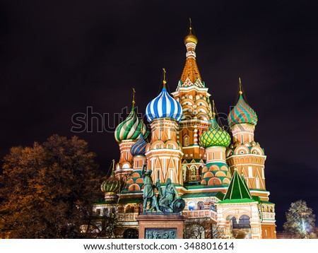 Saint Basil's (Vasily the Blessed, Pokrovsky) Cathedral and Monument to Minin and Pozharsky illuminated in night, on Red Square of Moscow - stock photo
