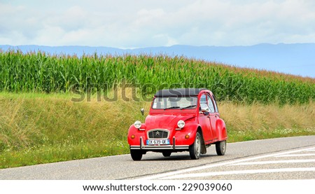 SAINT-BLAISE, FRANCE - AUGUST 7, 2014: Retro car Citroen 2CV at the interurban road. - stock photo
