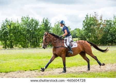 Saint Cyr du Doret, France - July 29, 2016: Rider on her galloping horse during a cross country manisfestation
