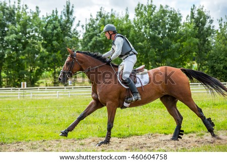 Saint Cyr du Doret, France - July 29, 2016: Rider on his galloping horse during a cross country manisfestation