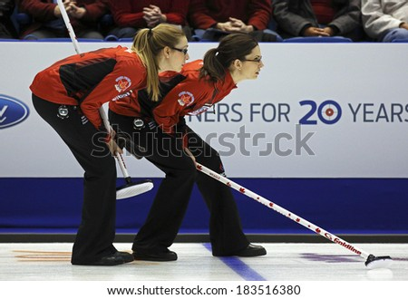 SAINT JOHN, CANADA - March 19: Alison Kreviazuk and Lisa Weagle of Canada follow an opponent's shot at the Ford World Women's Curling Championship March 19, 2014 in Saint John, Canada. - stock photo