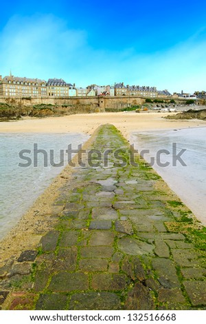 Saint Malo beach and stone pathway during Low Tide. Brittany, France, Europe. - stock photo