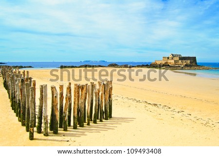 Saint Malo beach, Fort National and wooden poles during Low Tide. Brittany, France, Europe. - stock photo