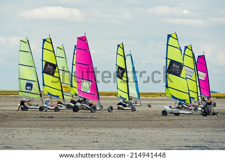 SAINT MALO, FRANCE - AUGUST 5, 2014: Land sailing on the a beach. Historically, land sailing was used as a mode of transportation or recreation. Since the 1950s it has evolved into a racing sport. - stock photo