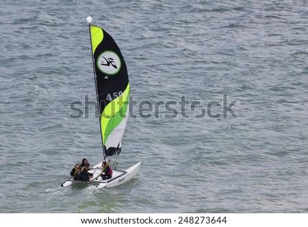 SAINT-MALO, FRANCE - JULY 6, 2011: Four teenage girls catamaran sailing on the coast of Saint-Malo. Their Hobie Cat 15 catamaran is 15 feet long and has a great buoyancy. - stock photo