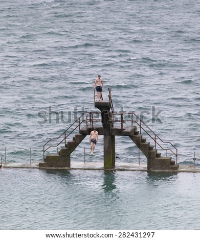 SAINT-MALO, FRANCE - JULY 6, 2011: Young man jumping into seawater pool. Another man is waiting on the diving platform.