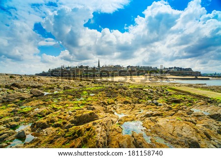 Saint Malo rampart skyline from beach rocks during Low Tide. Brittany, France, Europe. - stock photo