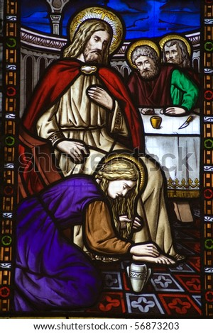 Saint Mary Magdalen footwashing Stained Glass Window A Victorian stained glass window depicting Saint Mary Magdalen anointing the feet of Jesus Christ and washing them with her hair. - stock photo