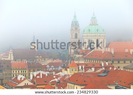 Saint Nicholas Church (Cathedral) and orange roof tops in foggy weather, Prague, Czech Republic - stock photo