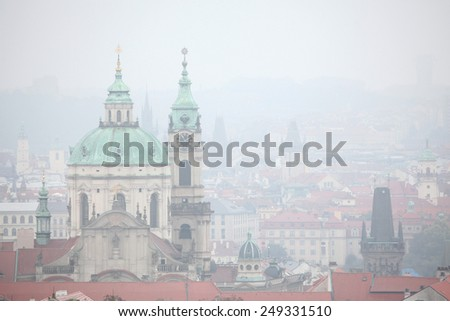 Saint Nicholas Church in Mala Strana viewed in the mist from Petrin Hill in Prague, Czech Republic. - stock photo