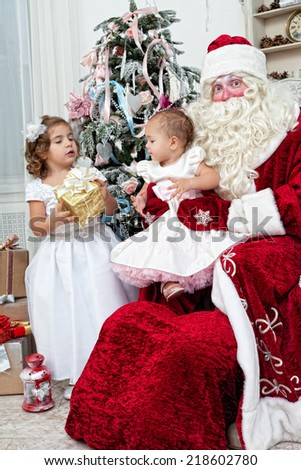 Saint Nicolas gives to small children Christmas gifts - stock photo
