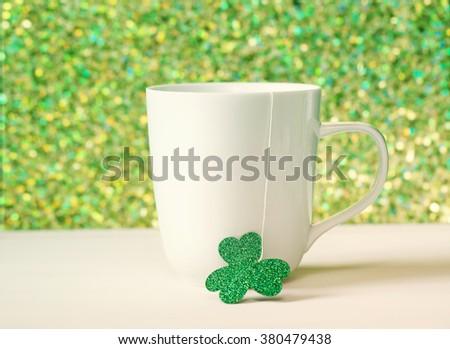 Saint Patricks Day green clover with white mug - stock photo