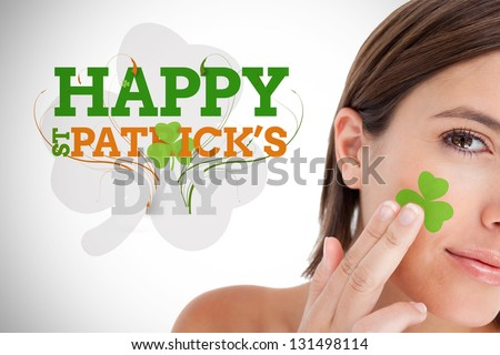 Saint patricks day greeting with smiling woman with shamrock on face - stock photo