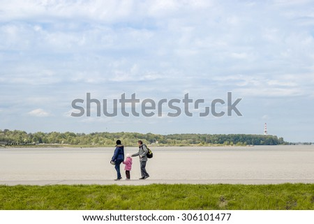 SAINT PETERSBURG - CIRCA MAY, 2015: Family Takes a Leisure Walk by the Lake