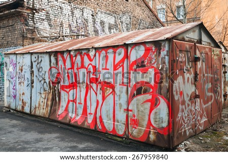 Saint-Petersburg, Russia - April 3, 2015: Old rusted locked abandoned garage with colorful chaotic grungy graffiti. Vasilievsky island, Central old part of St. Petersburg city - stock photo