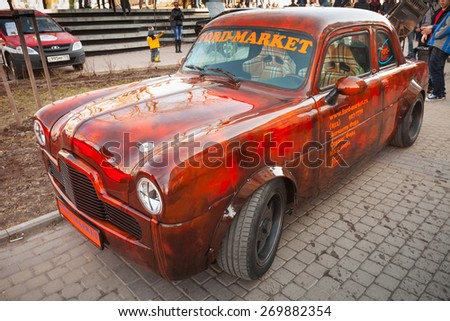 Saint-Petersburg, Russia - April 11, 2015: Small bright red Ford Zephyr 1955 car with tuning and aggressive sports design stands parked on the city street - stock photo