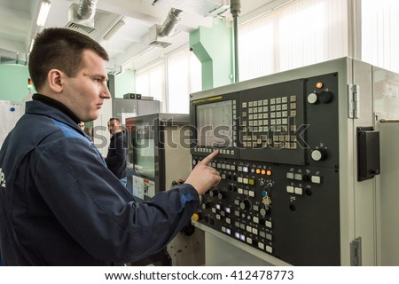 Saint-Petersburg, Russia - April 18, 2016: Turner is working on a lathe CNC. Man Caucasian 30-35 years is in the shop metal factory. close-up of the control panel.