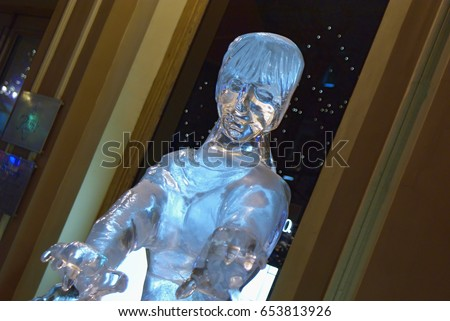 SAINT PETERSBURG, RUSSIA - FEBRUARY, 2010: Ice sculpture of a girl on a dark background. Exhibition of icy sculptures outdoors.