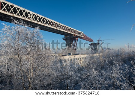 Saint-Petersburg, Russia - January 23, 2016: Construction of the city expressway highway. The high bridge over the sea in the harbor of the island Kanonersky area. Winter, a bright sunny day.
