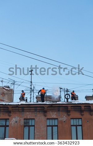 SAINT PETERSBURG, RUSSIA, 16 JANUARY 2016: Man removing snow from a roof with a snow shovel