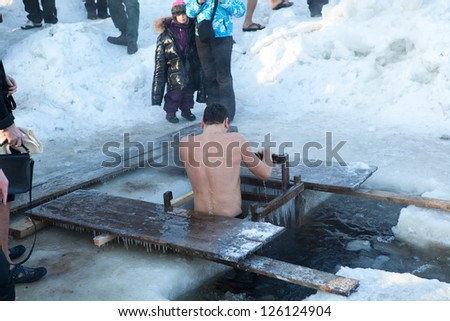 SAINT-PETERSBURG, RUSSIA-JANUARY 19: People in ice-hole dip three times in Epiphany celebration on January 19, 2013 in Saint-Petersburg, Russia.  Orthodox tradition in Epiphany (Holy Baptism)