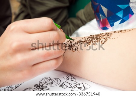Saint-Petersburg, Russia - July 19, 2015: Brown henna paste or mehndi application on woman hand, traditional Indian natural skin decoration