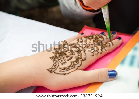 Saint-Petersburg, Russia - July 19, 2015: Henna paste or mehndi application on woman hand, traditional Indian natural skin decoration