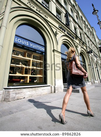 SAINT PETERSBURG, RUSSIA - JUNE 15: An upscale shopper walk by a Louis Vuitton store in Saint Petersburg, Russia on Wednesday, June 15, 2011 - stock photo