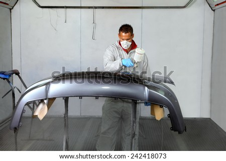 Saint Petersburg, Russia - June 26, 2014: Painting bumper car spray booth auto repair shop, working in a protective mask and clothing, operates a spray gun.