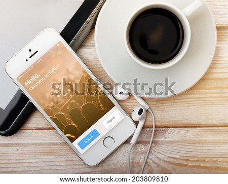 SAINT-PETERSBURG, RUSSIA - March 31, 2014: Photo of  iPhone 5 with home screen of popular social media website Twitter. iPhone 5S is a smartphone developed by Apple Inc.   - stock photo