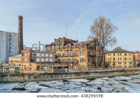 Saint Petersburg, Russia, March 23, 2016. The Ekateringofka river embankment at the ice drift and the view of the old industrial buildings.