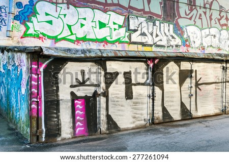 Saint-Petersburg, Russia - May 6, 2015: Old rusted locked abandoned garages with grungy graffiti. Vasilievsky island, Central old part of St. Petersburg city - stock photo