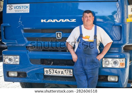 Saint-Petersburg, Russia - May 30, 2015: Positive truck driver stands near his blue Kamaz lorry cabin - stock photo