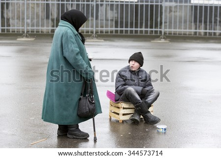 Saint Petersburg, Russia - November 20, 2015: An old woman and a man are begging for money in front of a church in St. Petersburg, Russia.