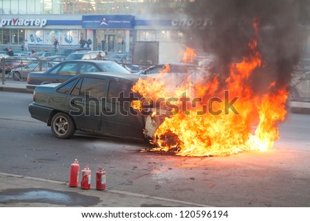 SAINT-PETERSBURG, RUSSIA-NOVEMBER 11: Burning car is on city street with used extinguishers on November 11, 2012 in Saint-Petersburg, Russia. Self-ignition car wiring. No one was injured.