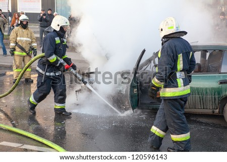 SAINT-PETERSBURG, RUSSIA-NOVEMBER 11: Firefighters are near burned car on city street on November 11, 2012 in Saint-Petersburg, Russia. Self-ignition car wiring. No one was injured.