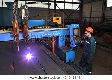 Saint  Petersburg, Russia - October 10, 2014: The metal factory, a worker operates a system of thermal cutting of metal sheets, plasma cutting machine for sheet steel, industrial equipment.  - stock photo