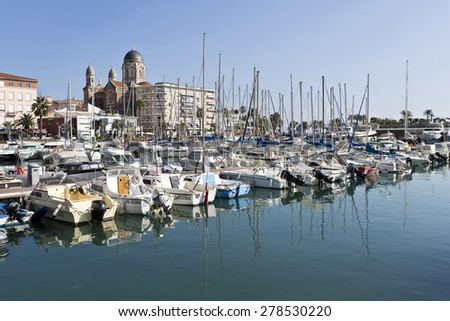 SAINT-RAPHAEL, FRANCE - SEPTEMBER 12, 2014: View of the Mediterranean Coast village of Saint-Raphael. Behind, the dome and the bell towers of the Basilica of Our Lady of Victory of Lepanto - stock photo