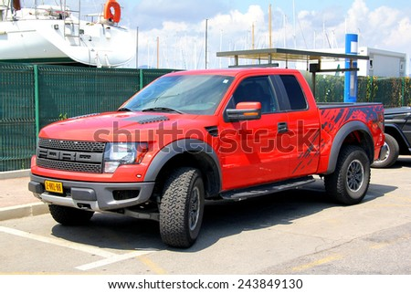 SAINT-TROPEZ, FRANCE - AUGUST 3, 2014: Red american pickup car Ford F150 Raptor at the city street. - stock photo
