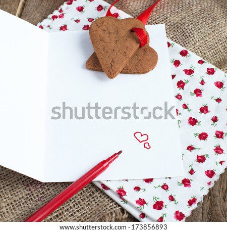 Saint Valentine's Love letter with heart shape cookies, hearts and red felt pen in rustic style
