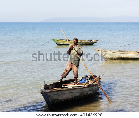 SAINTARD, HAITI -  An unidentified Haitian fisherman standing on his boat as he pushes away from the shore with a long pole near Saintard, Haiti on March 2, 2016. - stock photo