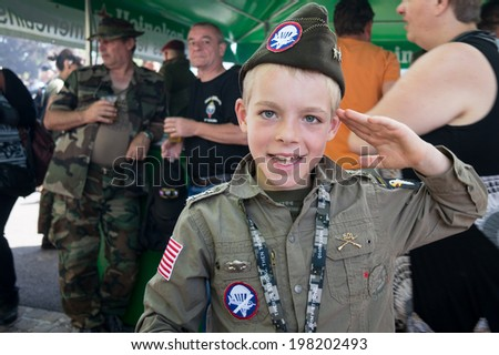SAINTE-MERE-EGLISE, FRANCE - JUNE 6, 2014: Child salutes in the uniform of American army in the Second World War during the commemoration of the 70th anniversary of D-Day.