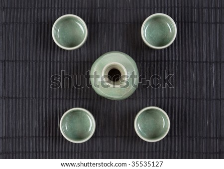 Sake flask and 4 cups on black - stock photo