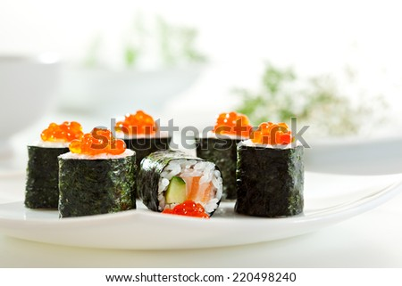 Sake Maki Sushi - Roll with Fresh Salmon and Cucumber inside. Topped with Salmon Caviar - stock photo