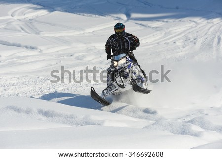 "SAKHALIN RUSSIAN - JANUARY 23 : Arkadiy Rybak moving snowmobile in winter forest in the mountains of Sakhalin Island in ""Sakhalin sprint 2015""  on  January 23, 2015 in Sakhalin Russia"