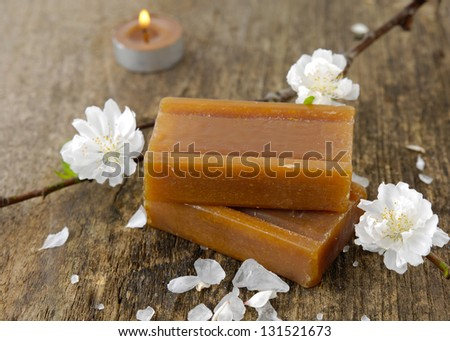 Sakura blossoms with stacked soap, candle on driftwood