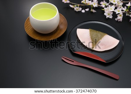 Sakura mochi, green tea and cherry branch on the black background. Sakura mochi is a kind of Japanese traditional confectionery shaped of the petal of cherry blossom and wrapped with a cherry leaf. - stock photo